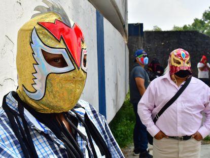 Un grupo de luchadores acude a las oficinas de la Comisión de lucha libre para recibir apoyos frente a la pandemia de la covid-19.