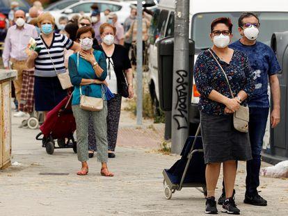 Varias personas hacen cola guardando las distancias de seguridad en un mercadillo junto al Palacio del Hielo en Madrid, este martes.