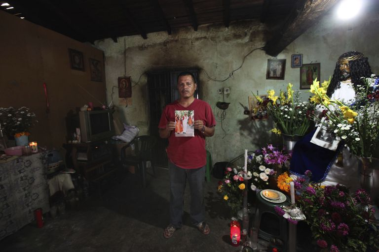 Clemente Rodríguez, father of the normalista identified a few weeks ago.  In the image, taken in 2014, Clemente poses at home with a photo of his son.