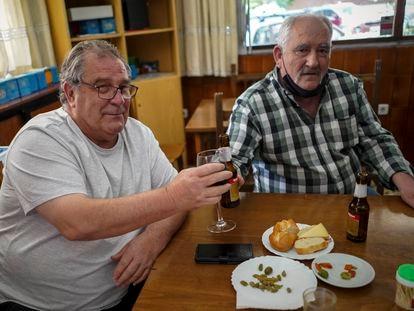 Juan Flores, de 68 años (izquierda), brinda con su cuñado, Jesús García, de 66, en el bar JF 83 de Fuenlabrada.