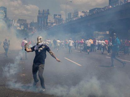 Un manifestante devuelve un bote de gas lacrimógeno durante el enfrentamiento con la Policía Nacional Bolivariana (PNB), en una protesta contra el gobierno de Nicolás Maduro, en Caracas (Venezuela).