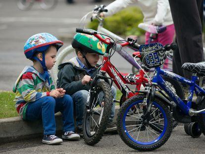 Dos niños se sientan en la acera junto a sus bicicletas,