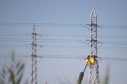 Varios operadores están trabajando en una línea eléctrica en las afueras de Sevilla.