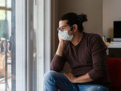 Un hombre mira pensativo a través de la ventana de su casa.