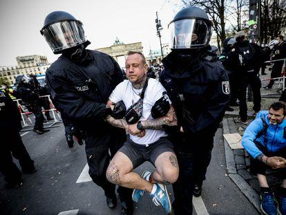 La policía se lleva detenido a un manifestante en la protesta de este miércoles en Berlín contra las nuevas restricciones que ha aprobado el Parlamento alemán.
