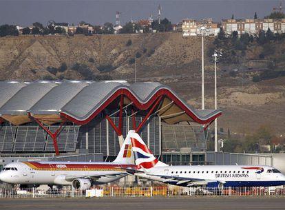 Un avión de Iberia y otro de British Airways, en la T-4 del aeropuerto de Barajas (Madrid).