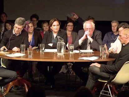 Reunião da Internacional Progressista com Ada Colau no centro, Bernie Sanders a sua esquerda e Yanis Varoufakis de perfil.