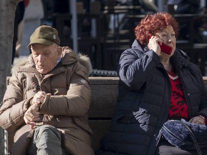 Un hombre y una mujer, ambos de avanzada edad, sentados en el centro de Sevilla.