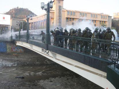 Carabineros observan a un manifestante que se encuentra inconsciente tras caer en el río Mapocho, en Santiago (Chile).