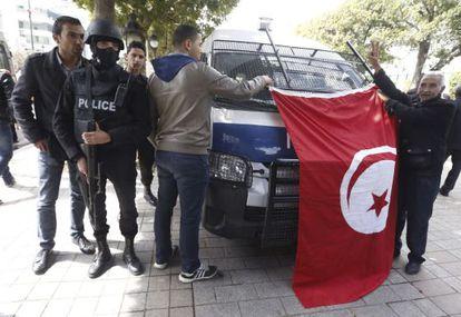 Dos hombres enseñan una bandera tunecina junto a un policía, en el centro de Túnez, este viernes.