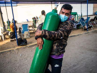 Un hombre carga con un tanque de oxígeno vacío mientras llega a la cola para rellenarlo en Villa El Salvador, en las afueras del sur de Lima.