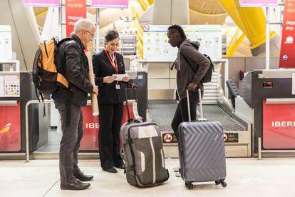 Unos pasajeros facturan en un mostrador de Iberia.