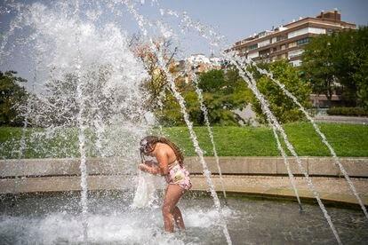 Una niña se baña en una fuente pública este miércoles en Madrid.
