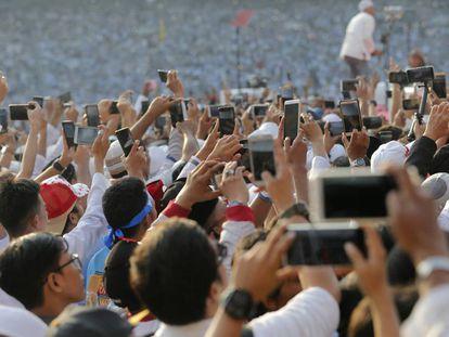 Docenas de móviles graban un mítin en Indonesia.