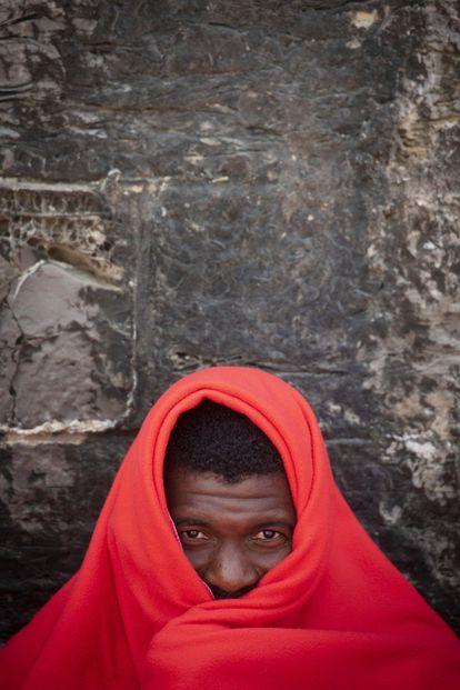 Un inmigrante espera a ser atendido en el puerto de Tarifa.