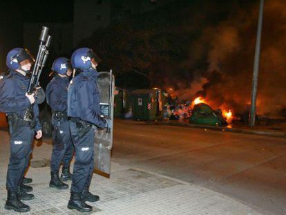 Agentes antidisturbios vigilan ante unos contenedores ardiendo.