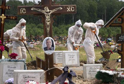 Empleados del servicio funenario ruso entierran a una víctima del coronavirus en el cementerio de Kolpino, a las afueras de San Petersburgo, el pasado junio.