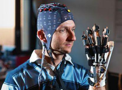 Un colaborador del profesor Millán lleva puesta la capucha de electrodos y practica para mover una mano con la mente.