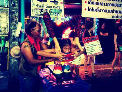 Una niña hace ejercicios de contorsionismo junto a un club de 'striptease' en Pattaya, Tailandia.