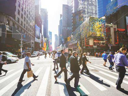 Varias personas cruzan la Séptima Avenida de Nueva York.