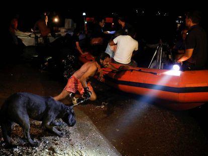 Un hombre sujeta a un perro y empuja una barca hinchable en Mati, durante los desalojos por los incendios.