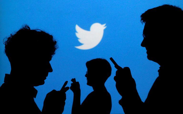 El logotipo de Twitter y algunas personas con sus móviles.