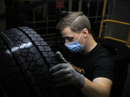 Un trabajador inspecciona un neumático de automóvil en el centro de distribución de Continental Tire, en marzo.