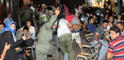 Un policía carga contra participantes en las protestas del 2 de agosto en Marruecos contra el indulto del pederasta español.