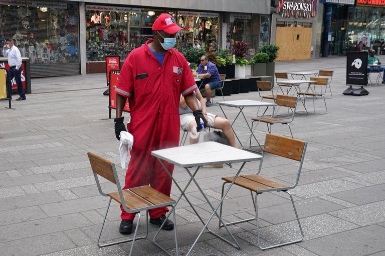 Un operario limpia una mesa de una terraza casi vacía en Times Square a finales de junio.