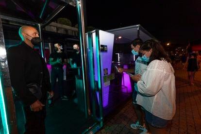 Dos personas esperan para poder acceder a un local en Sansenxo, el 16 de julio.