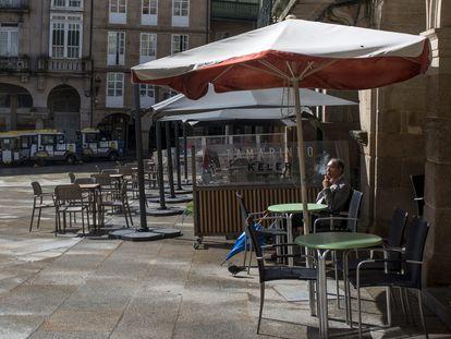 Un hombre fuma sentado en una terraza en la Plaza Mayor de Ourense.