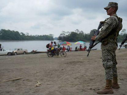 Dos militares colombianos patrullan junto al río Mira, cerca de la frontera con Ecuador.