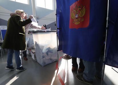 Una mujer deposita las papeletas de votación en un colegio electoral de San Petersburgo, este domingo.