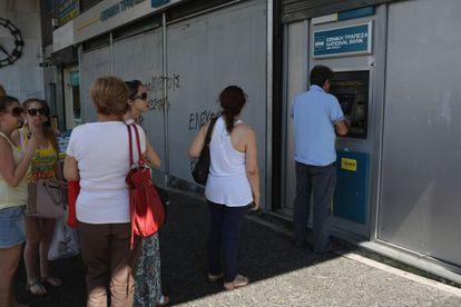 Gente hace cola este lunes en un cajero automático de Atenas.