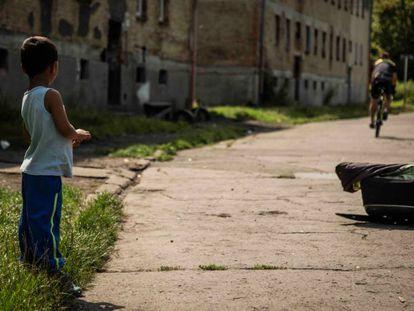 Un niño gitano observa a un ciclista, en un barrio marginado de Ostrava.