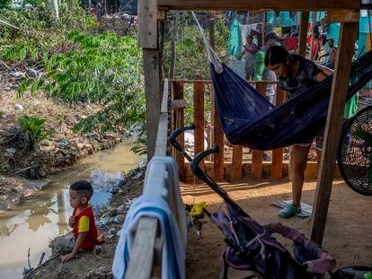 La venezolana Alexandra Andrade, de 16 años, mece a su niño en el asentamiento irregular del 12 de septiembre, en Tibú, frente al caño de aguas negras que rodea su casa.