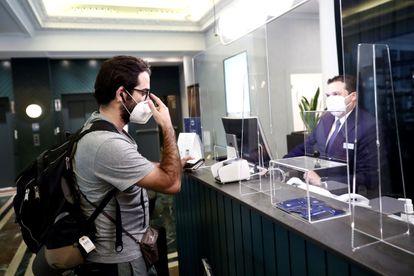 Un recepcionista de hotel atiende a un cliente con mascarilla y mampara de por medio en junio de 2020.