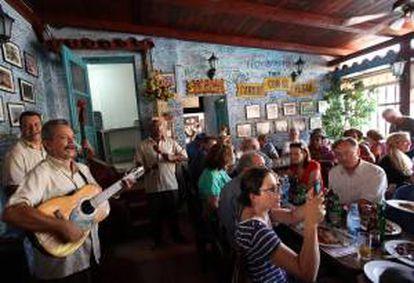 """En total, Cuba recibió a 2.170.242 viajeros extranjeros en los primeros nueve meses del año, en los que la isla tuvo unos ingresos turísticos que superan los 1.412 millones de dólares. En la imagen el registro de varios turistas departiendo en la famosa """"Bodeguita del Medio"""", en La Habana (Cuba). EFE/Archivo"""