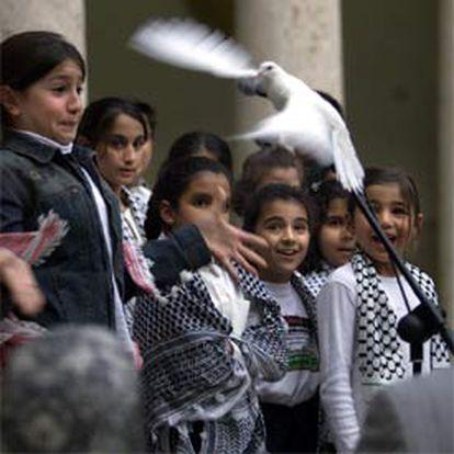 Una niña iraquí suelta una paloma en el acto ecuménico celebrado ayer en la Universitat de València.