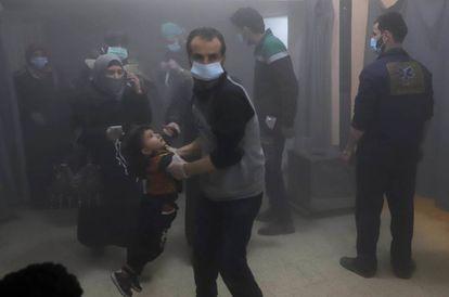 Ciudadanos sirios se protegen de los bombardeos del régimen, este martes en Zamalka, Guta Oriental.