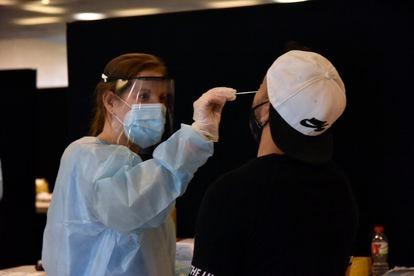 Una sanitaria realiza un test de antígenos a un joven en Barcelona.