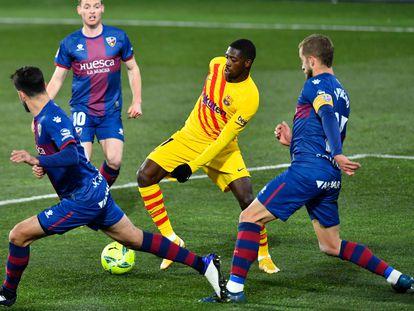Ousmane Dembélé busca un pase rodeado de defensores del Huesca.