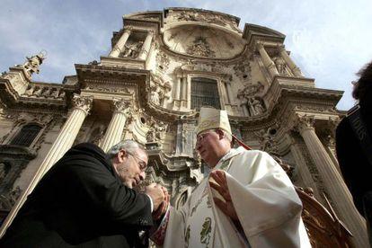 El presidente de la Universidad Católica de Murcia, José Luis Mendoza, besa la mano del obispo Reig Plà, en Murcia en 2008.