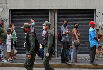 Personas con mascarillas observan a unos agentes de la policía en Caracas, Venezuela.