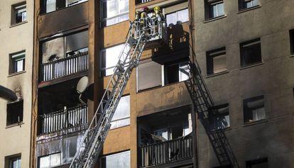 Los bomberos evacuan a vecinos del edifico quemado en Badalona.