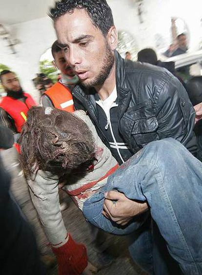 Un médico lleva en brazos a una niña palestina herida en la ciudad de Gaza por el bombardeo israelí.
