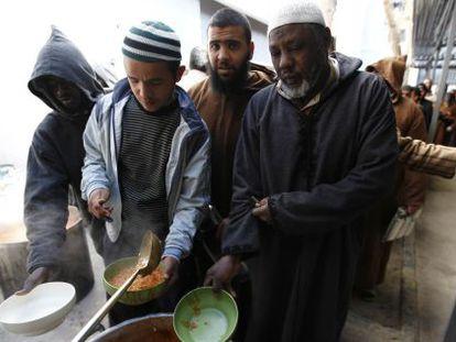 Presos de un centro de detención de Misrata hacen cola para recibir su ración de comida.