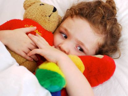 Niña pequeña en su cama abrazada a sus peluches