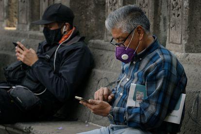 Dos hombres manejan su teléfono móvil en Ciudad de México.