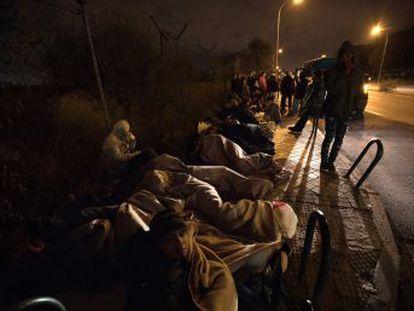 Familias y enfermos inmigrantes hacen cola frente a una comisaría
